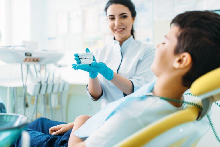 Female dentist shows dentures to little boy